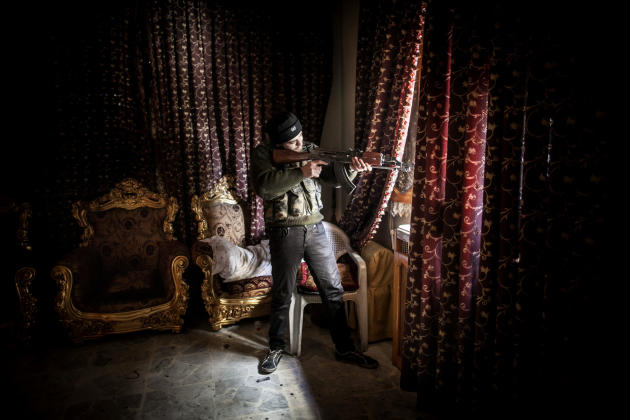 A Free Syrian Army fighter aims his weapon in the Saif al-Dawlah neighborhood of Aleppo, Syria, Sunday, Jan. 13, 2013. The revolution against the Syrian regime started in March 2011 with peaceful prot