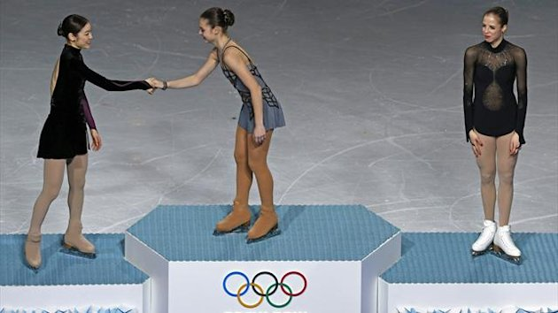 First-placed Russia's Adelina Sotnikova (C) shakes hands with second-placed South Korea's Kim Yuna (L) as third-placed Italy's Carolina Kostner looks on (Reuters)