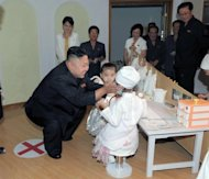 North Korean leader Kim Jong-Un talks to two children during a visit to the Kyongsang kindergarten in Pyongyang. Kim is accompanied by what appears to be the same woman (wearing yellow polka dot dress) who has been seen at recent public events. The reappearance of the mystery brunette has increased speculation that she could be his wife