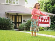 real estate agent with for sale sign in front of house