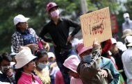 A garment worker holds a placard during a protest in central Phnom Penh December 31, 2013. REUTERS/Samrang Pring