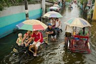 People use pedicabs to cross floodwaters in a street in Valenzuela, on the outskirts of Manila. The Philippine capital is braced for more wet weather and authorities rushed relief supplies to the remote northern Philippines as a new storm -- expected to trigger flashfloods and landslides -- closed in
