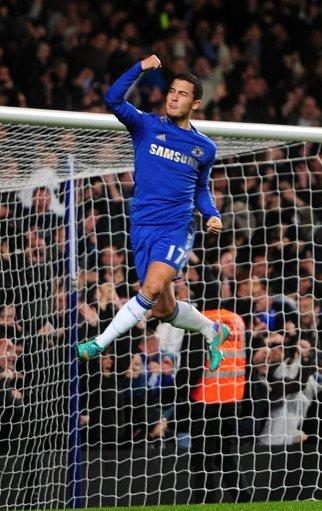 Eden Hazard leaps into the air after his spot-kick ensured the game went to extra time