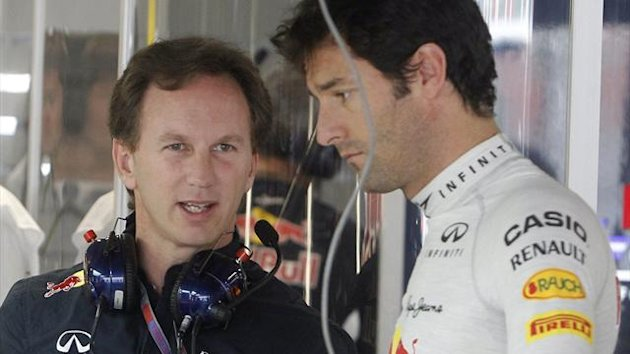 Red Bull Formula One driver Mark Webber of Australia talks to team principal Christian Horner inside their team garage