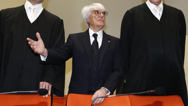 F1 CEO Bernie Ecclestone, center, stands with his lawyers as he arrives in the court in Munich, southern Germany, Thursday, April 24, 2014. Ecclestone is charged with bribery and incitement to breach