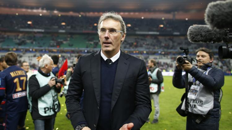 Paris St Germain's coach Blanc looks on while he celebrates defeating Olympique Lyon in the French League Cup final soccer match in Saint-Denis, near Paris