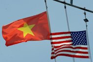 Vietnamese and US flags are seen flying atop a US ship in Tien Sa port, Vietnam in April 2012. Vietnam's president on Wednesday starts a rare visit to Washington to boost trade and security ties between the former war foes, but activists urged the United States to press him on human rights