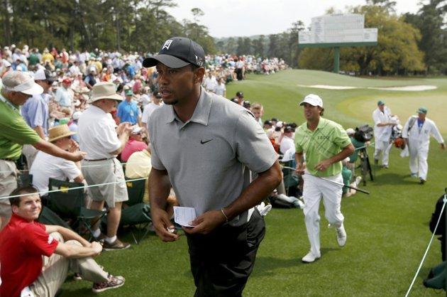 Tiger Woods of the U.S. carries his scorecard as he leaves the 18th green during first round play in the 2013 Masters golf tournament in Augusta