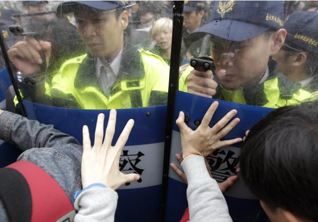 Anti-nuclear activists scuffle with police officers during a protest in Taipei