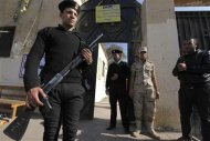 Egyptian police and a soldier stand guard outside a polling station during a referendum on the new constitution in Cairo, January 15, 2014. REUTERS/Mohamed Abd El Ghany