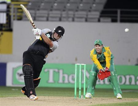 New Zealand's Ryder bats as South Africa's Villiers looks on during their Twenty20 international cricket match in Auckland
