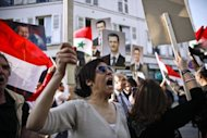 Supporters of the Syrian regime hold portraits of Syrian President Bashar al-Assad as they demonstrate in front of the Syrian cultural center in Paris
