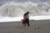 A couple walks along the beach in Nanfangao, eastern Ilan county, as typhoon Saola approaches Taiwan's east coast on Tuesday. Taiwan Tuesday warned that the typhoon was likely to bring heavy rains and trigger landslides on the island after it killed eight people in the Philippines