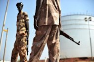 South Sudanese soldiers stand next to crude oil reservoir tanks at a field processing facility in Unity State on November 11, 2010. South Sudan has restarted oil production, ending a bitter 15-month row with former civil war foe Sudan and marking a major breakthrough in relations after bloody border clashes last year