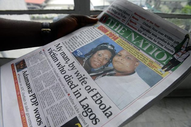 A man reads a newspaper featuring a front page story on the death of Liberian diplomat Patrick Sawyer (pictured with his wife Decontee) who died of the Ebloa virus in Lagos on July 30, 2014