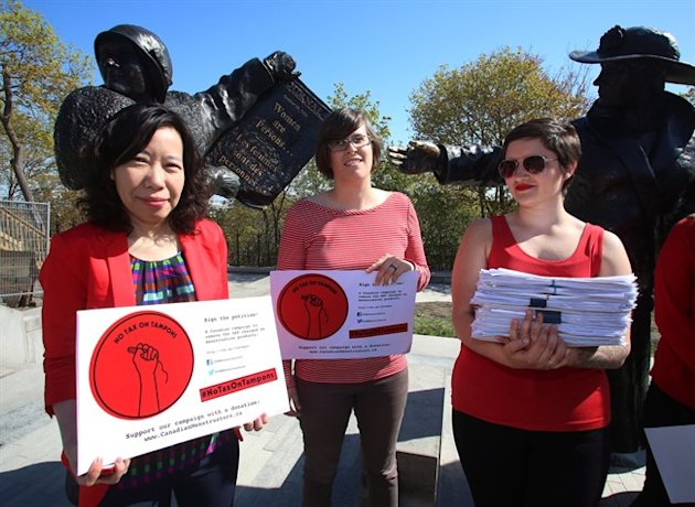 Lele Truong, Lareen Jervis and Mariana Hollmann (left to right) take part in a news conference and petition on Parliament Hill in Ottawa Thursday, May 7, 2015 calling on the federal government to remove tax on feminine hygiene products. THE CANADIAN PRESS/Fred Chartrand