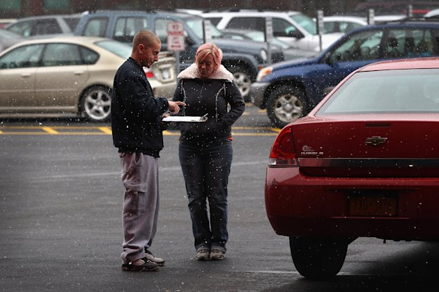 Recovery Agent Amanda Husted (R), returns a vehicle to an owner after he paid for its release. (Getty)