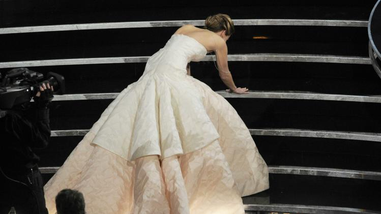 Jennifer Lawrence stumbles as she walks on stage to accept the award for best actress in a leading role for