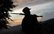 A rebel fighter is seen on patrol outside a town in Myanmar's northern Kachin state, on September 22, 2012. Kachin rebels cast doubt on Saturday over a Myanmar government pledge to end a military offensive after weeks of intense fighting that sparked international concern amid reports of fresh shelling