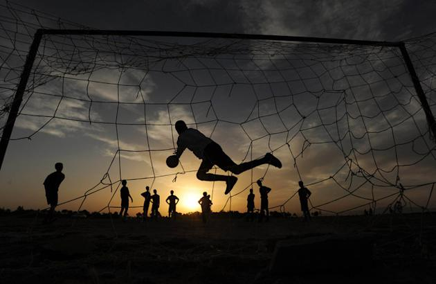 TOPSHOTS Afghan Youth Play Football In The Evening In The City Of Herat On May 19, 2012. AFP PHOTO/ Aref KarimiAref AFP/Getty Images
