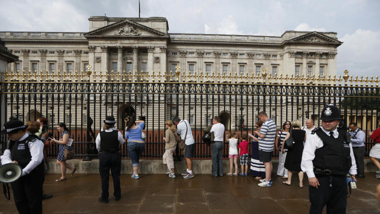People queue to look at a notice proclaiming the birth of a baby boy of Prince William and Kate, Duchess of Cambridge on display for the public view at Buckingham Palace in London, Tuesday, July 23, 2013. (AP Photo/Sang Tan)