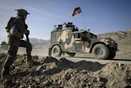 A French soldier watches an Afghan military vehicle in Afghanistan's Kapisa Province. The French military has officially handed over control of the key Afghan province of Kapisa to Afghan forces