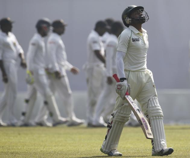 Bangladesh's captain Mushfiqur Rahim leaves the field as Sri Lanka's fielders celebrate his dismissal during their fourth day of their first test cricket match of the series in Dhaka.