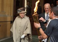 Britain's Queen Elizabeth II (L) and her husband Prince Philip look at the Olympic Flame at Windsor Castle in London on July 10. The 86-year-old monarch will officially open the Games at Friday's Olympic opening ceremony