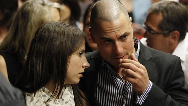 Oscar Pistorius's sister Aimee and brother Carl await the start of court proceedings in the Pretoria Magistrates court, February 19, 2013 (Reuters)