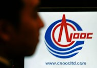 An employee of China National Oil Offshore Company (CNOOC) looks at the company's logo during a press briefing at a hotel in Hong Kong, on January 23, 2006. CNOOC completed its $15.1 billion purchase of Canada's Nexen energy group on Monday, in what analysts have said is China's largest foreign investment