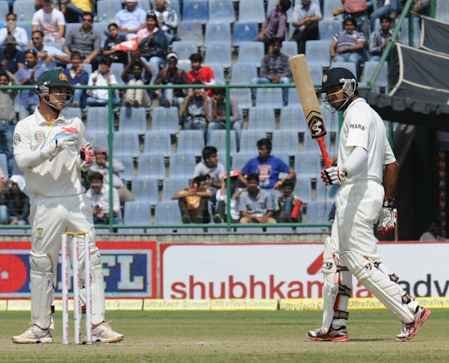 India's Cheteshwar Pujara raises his bat to acknowledge applause for his half century on Day two of the 4th Test of the Border-Gavaskar Trophy, at Feroz Shah Kotla Stadium in Delhi on March 23, 2013.