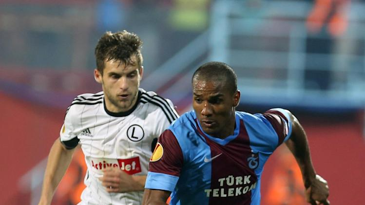 Trabzonspor's Malouda, left, and Broz of Legia fight for the ball during their Europa League Group J soccer match in Trabzon, Turkey, Thursday Oct. 24, 2013. (AP Photo)