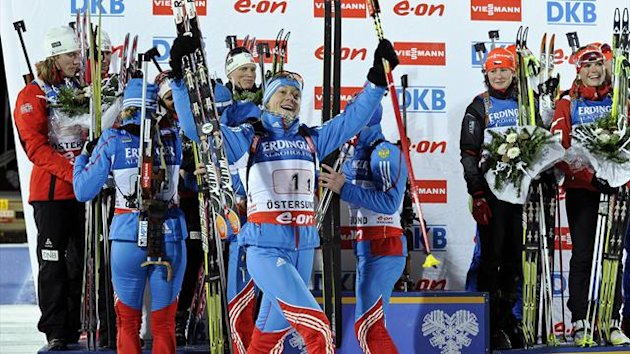Russia's Olga Zaitseva (front) celebrates as the Russian team (blue) make their way to the podium after winning the Mixed Relay event at the Biathlon World Cup in Ostersund, Sweden (Reuters)