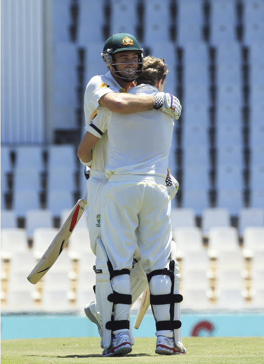 Australia's batsman Shaun Marsh, back, embraces teammate Steven Smith for reaching his century on the second day of their cricket test match against South Africa at Centurion Park in Pretoria, Sou