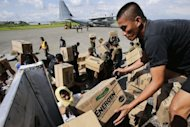 Philippine Army personnel unload relief goods at an airport in Mindanao on December 15, 2012. Typhoon Bopha killed 1,020 people, mostly on Mindanao island, where floods and landslides caused major damage on December 4, civil defence chief Benito Ramos said.