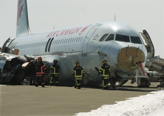 TSB investigators and airport firefighters work at the crash site of Air Canada AC624. (Canadian Press)