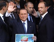 Silvio Berlusconi waves to supporters next to People of Freedom (PDL) Secretary Angelino Alfano (R) while showing the logo of his re-launched political party, Forza Italia (Go Italy), in downtown Rome, September 19, 2013. REUTERS/Alessandro Bianchi