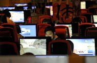 People surf the internet in a cafe in Beijing in 2011. A Chinese military official has been suspended and placed under investigation over accusations of a drunken assault on a flight attendant after pictures of her alleged injuries emerged on Sina Weibo, state media said Tuesday. China has the world's largest online population with more than half a billion users, a challenge to government control