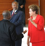 Uganda President Yoweri Museveni (L) chats with Brazilian President Dilma Vana Rousseff (R) as Djiboutian counterpart Osman Omar Guelleh (C) looks on, during a summit marking the 50th anniversary of the founding of the African Union, in Addis Ababa, Ethiopia, on May 25, 2013. Brazil announced it was cancelling $900 million (700 million euro) worth of debt in 12 African countries
