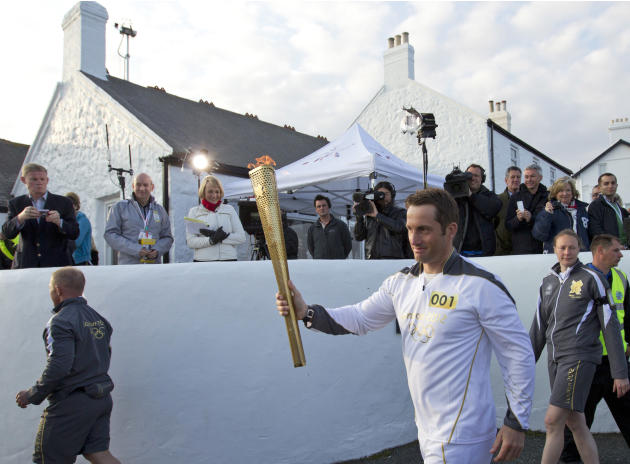 British Olympic sailing hero and three time gold medalist Ben Ainslie walks past the media as he holds the Olympic torch at the official start of the London 2012 Olympic games torch relay at Land's En