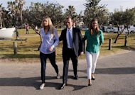 Tony Abbott (C), who leads the conservative opposition, arrives with his daughters Bridget (L) and Frances to cast his vote on election day at the Freshwater Beach Surf Lifesaving Club in Sydney September 7, 2013. REUTERS/David Gray