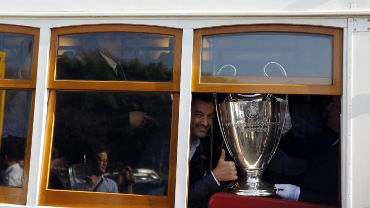 Former Portuguese soccer player Vitor Baia poses with the Champions League trophy on a tram during a parade around the city in Lisbon