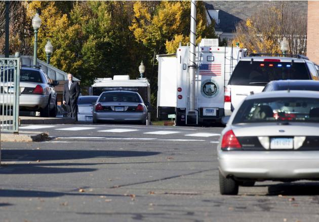 Law enforcement vehicles line the roadway to Central Connecticut State University while it is in lockdown in New Britain
