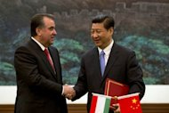 Tajikistan President Emomali Rahmon (left) and Chinese President Xi Jinping shake hands after signing an agreement in Beijing on May 20, 2013. At a regional summit, Xi signed a deal to build a gas pipeline through the impoverished ex-Soviet country, Tajik television has reported