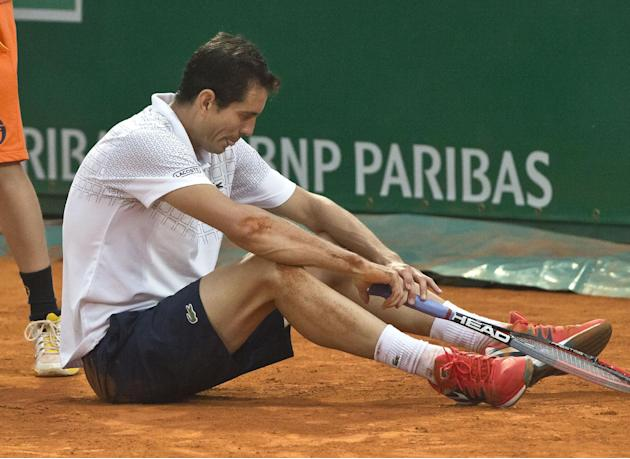 Guillermo Garcia-Lopez of Spain sits on the ground as he plays against Novak Djokovic of Serbia during their quarterfinals match of the Monte Carlo Tennis Masters tournament in Monaco, Friday, April 1