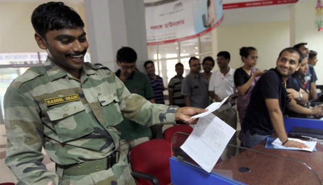 An Indian army soldier reacts as he prepares to send a telegram on the last day of the 163-year-old service at a telegraph office in Kolkata, India, Sunday, July 14, 2013. Sunday night, the state-run