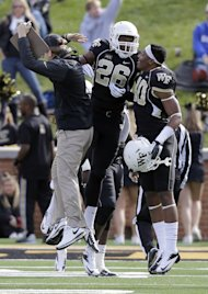 Wake Forest safety Thomas Brown (26) celebrates his fumble return for a touchdown against Duke with Marquel Lee (40) and an assistant coach, left, during the first half of an NCAA college football game in Winston-Salem, N.C., Saturday, Nov. 23, 2013. (AP Photo/Chuck Burton)