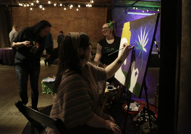 Nelson paints a marijuana leaf at the Cannabis Carnivalus 4/20 event in Seattle