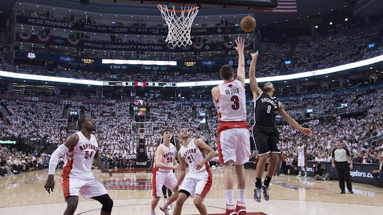 Brooklyn Nets' Deron Williams, right, shoots over Toronto Raptors' Nando De Colo during the second half of Game 1 of an opening-round NBA basketball playoff series, in Toronto on Saturday, April 19, 2014. The Nets won 94-87