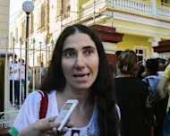 Cuban opposition blogger Yoani Sanchez speaks with the press outside a Migration Office, on January 14, 2013 in Havana. A law allowing Cubans to travel abroad without special exit visas took effect on the communist-ruled island for the first time in half a century